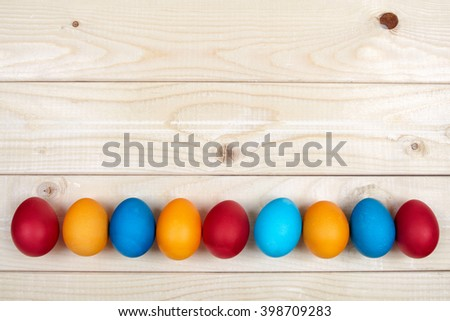 Colorful Easter egg frame on light wooden boards. A row of hand dyed eggs below a copy space