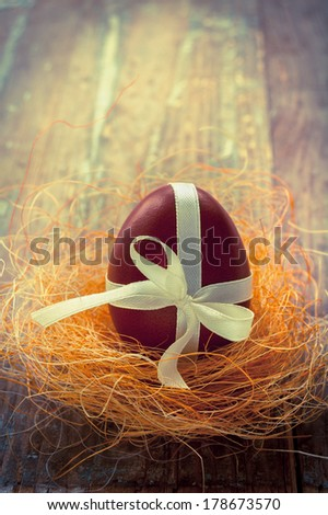 Colorful easter egg in the nest on the dark wooden background - stock photo