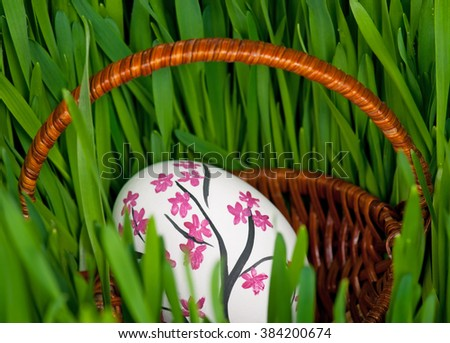 Colorful Easter egg over bright green grass on the organic soil - stock photo