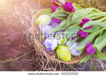 Colorful easter eggs and beautiful spring flowers laid on a floor. - stock photo