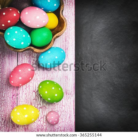 colorful easter eggs and cutlery on a black background. Focus on a wooden table. vignetting is used as an artistic device - stock photo