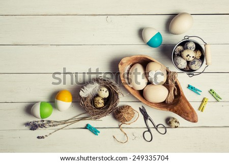 colorful easter eggs and decorations on white wooden table - stock photo