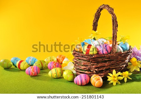 colorful easter eggs and narcissus in easter nest
