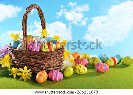 colorful easter eggs and narcissus in easterbasket on grass with sky - stock photo