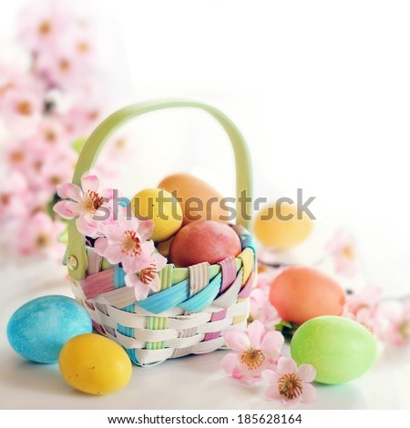 Colorful Easter eggs and pink spring flowers in a basket on white background - stock photo