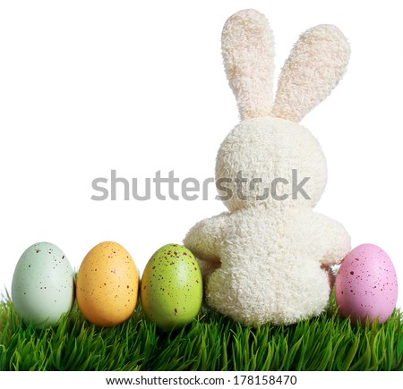 Colorful easter eggs and rabbit on grass, isolated on white - stock photo