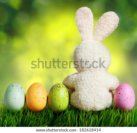 Colorful easter eggs and rabbit on green grass over bokeh - stock photo