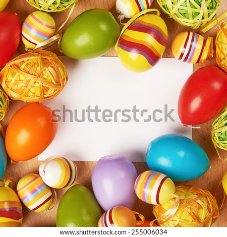 Colorful Easter eggs around the white copyspace paper card - stock photo