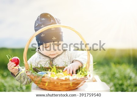 Colorful Easter eggs.Baby sits with Easter basket on grass.
