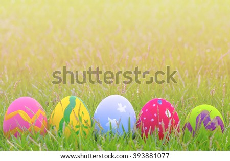 Colorful Easter eggs decorated with flowers in the grass on a yellow background .
