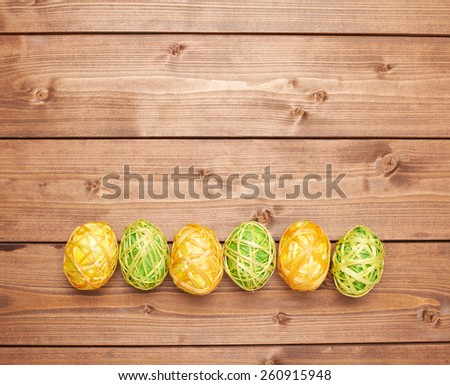 Colorful Easter eggs decoration lying ing line over the brown wooden surface as a copyspace festive background composition - stock photo