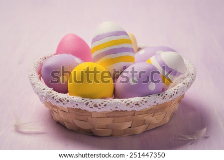 Colorful Easter eggs in a basket - stock photo
