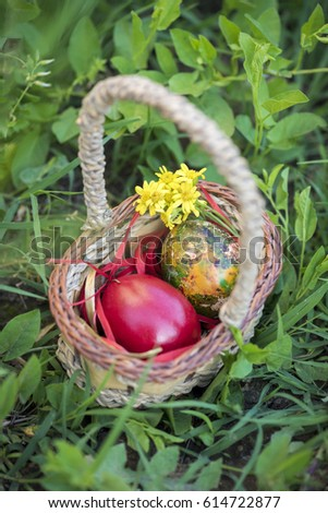 Colorful Easter eggs in a basket and green grass background