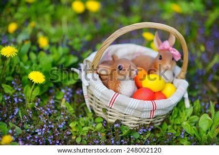 Colorful easter eggs in a basket on a grass with two bunnies - stock photo