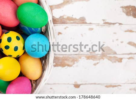 colorful easter eggs in a basket on old wooden background - stock photo