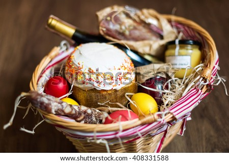 Gift basket colorful easter eggs in a basket with cake red wine jamon or jerky and negle Images