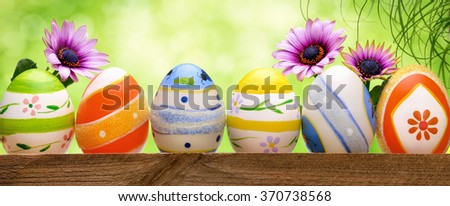 Colorful Easter eggs in a row, decorated with spring flowers and long grass, with bright green bokeh background, panorama format - stock photo