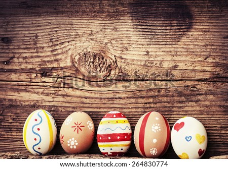 Colorful Easter eggs in a straight row on old wooden table background, Easter background - stock photo