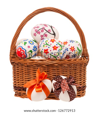 Colorful Easter eggs in a wicker basket isolated on white background