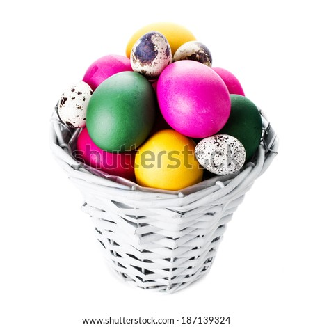 Colorful easter eggs in basket isolated on white background close up.  - stock photo