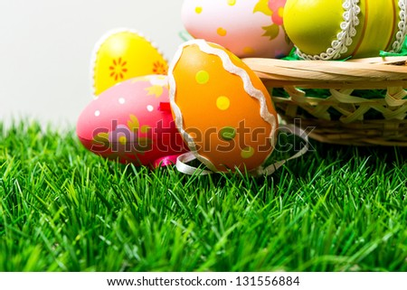 Colorful easter eggs in basket on spring green grass