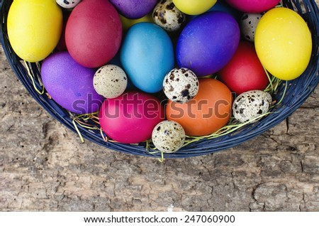 Colorful Easter eggs in basket on wooden background - stock photo