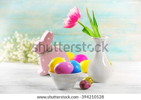 Colorful Easter eggs in bowl and fresh tulip on wooden background