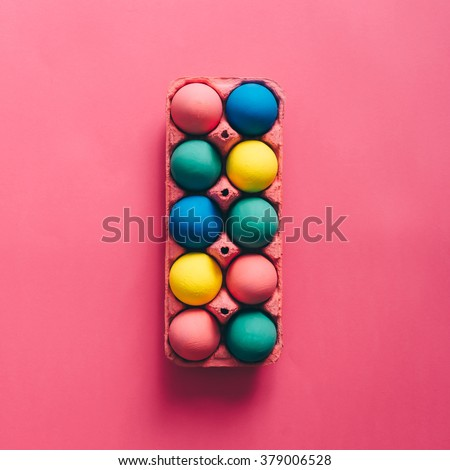 Colorful Easter eggs in box on pink background - stock photo