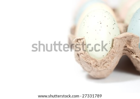 Colorful Easter eggs in cardboard crate on white background.