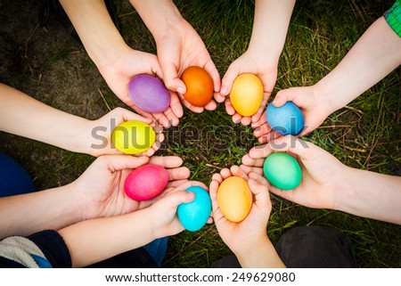 Colorful easter eggs in child hands after egg-hunt - stock photo