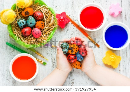 Colorful easter eggs in child hands after painting beautiful concept Easter background top view - stock photo