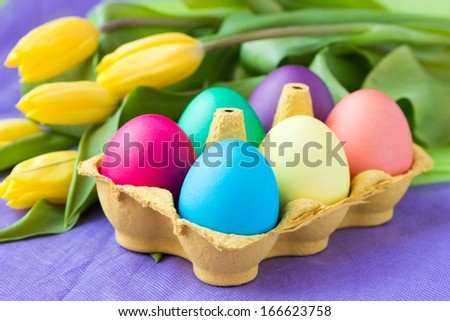 Colorful easter eggs in packing box with tulips flowers - stock photo