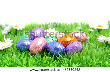 colorful easter eggs in plastic grass over white background
