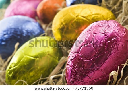 Colorful easter eggs in straw - close up with shallow depth of field - stock photo
