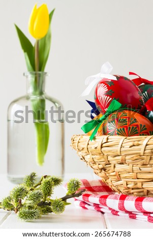 Colorful Easter Eggs in the basket with spring yellow tulip in the glass bottle and spring pussies, traditional decoration for this spring holiday - stock photo