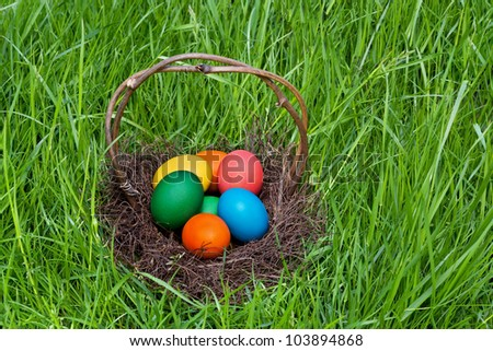 Colorful Easter eggs in the brown basket. - stock photo