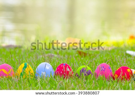 Colorful Easter eggs in the grass on the green water