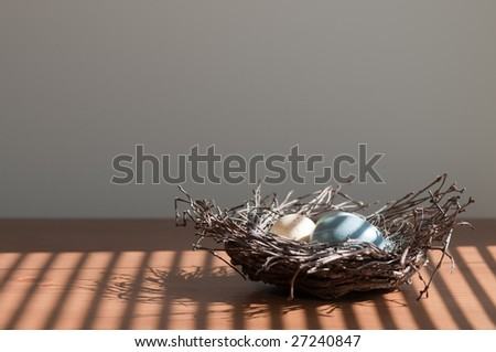 Colorful Easter eggs in twig nest, on wooden surface. Light by sunshine shining through horizontal blinds. - stock photo