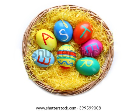 Colorful Easter eggs in wicker nest isolated on white