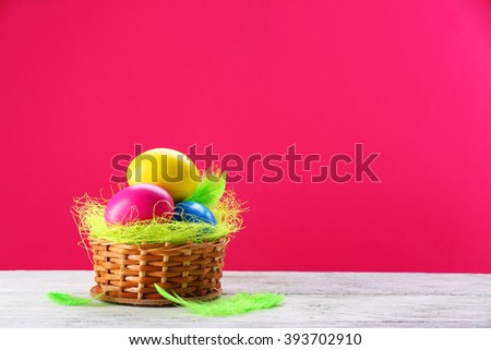 Colorful Easter eggs in wicker nest on pink background - stock photo