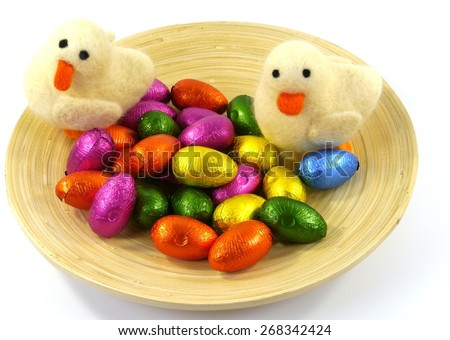 Colorful Easter eggs of chocolate and two decorative ducklings on a bowl of bamboo over white - stock photo