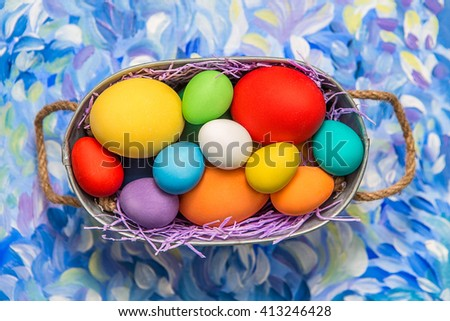 Colorful Easter eggs on bright background. Easter holiday. Multicolored background green, blue and purple colors. Easter eggs in a basket. - stock photo