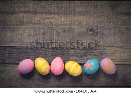 Colorful Easter Eggs on Dark Rustic Wood Background with room or space for text, copy.  Horizontal  - stock photo