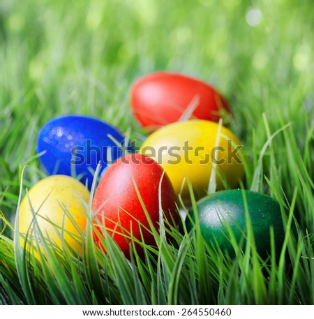 Colorful Easter eggs on green grass. Yellow, red, green and blue eggs painted for the Easter. Organic healthy eco food rich in minerals and vitamins. - stock photo
