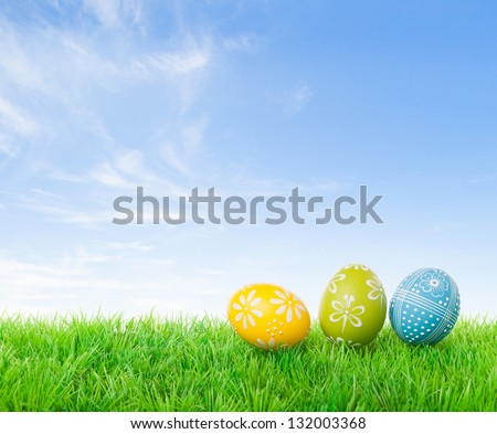 Colorful easter eggs on meadow over bright spring sky. - stock photo