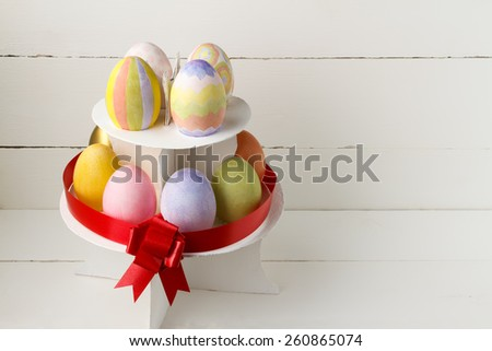 Colorful Easter eggs on stand with red ribbon against white background - stock photo