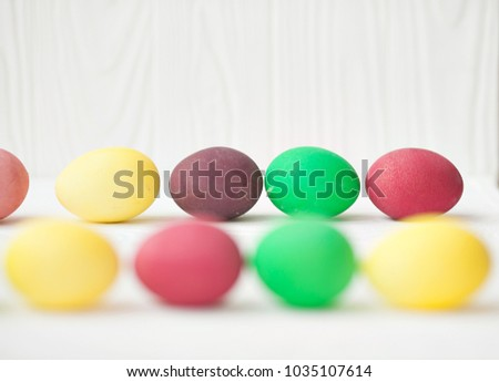 Colorful Easter eggs on white wooden background.
