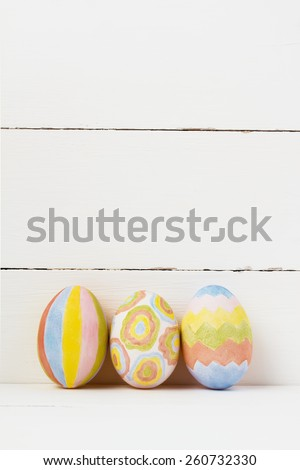 Colorful easter eggs on white wooden background copy space - stock photo