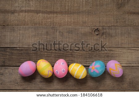 Colorful Easter Eggs on Wood Board Background with room or space for copy, text - stock photo