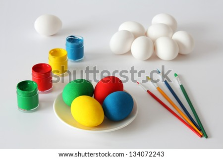 Colorful easter eggs, paints and brushes isolated on a white background.